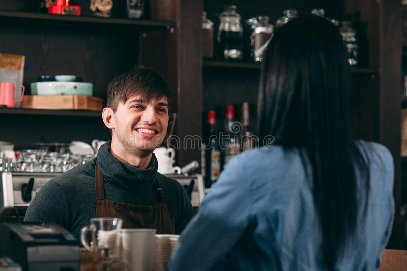 Männlicher Kassierer, der für junge Frau im Café lächelt lizenzfreie stockbilder