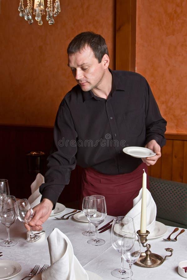 Männlicher Kellner ordnet Teller an stockbilder