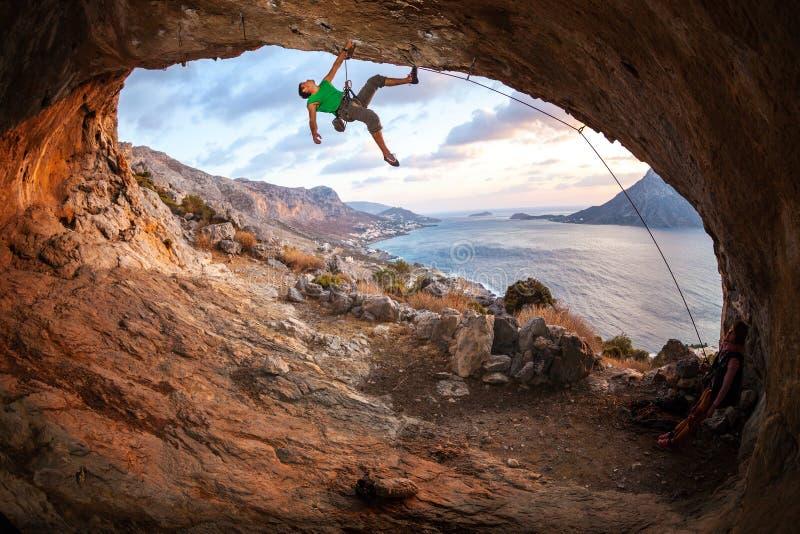 Männlicher Kletterer, der entlang einem Dach in einer Höhle klettert stockfoto