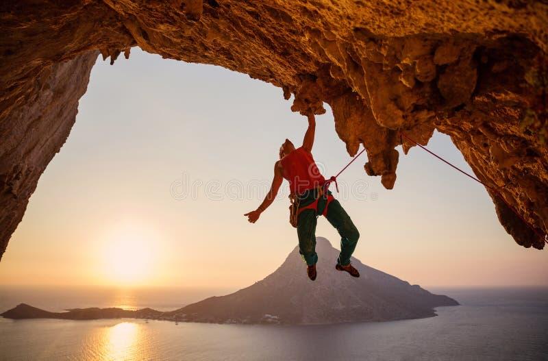 Männlicher Kletterer, der an der Klippe mit einer Hand bei Sonnenuntergang hängt lizenzfreie stockbilder