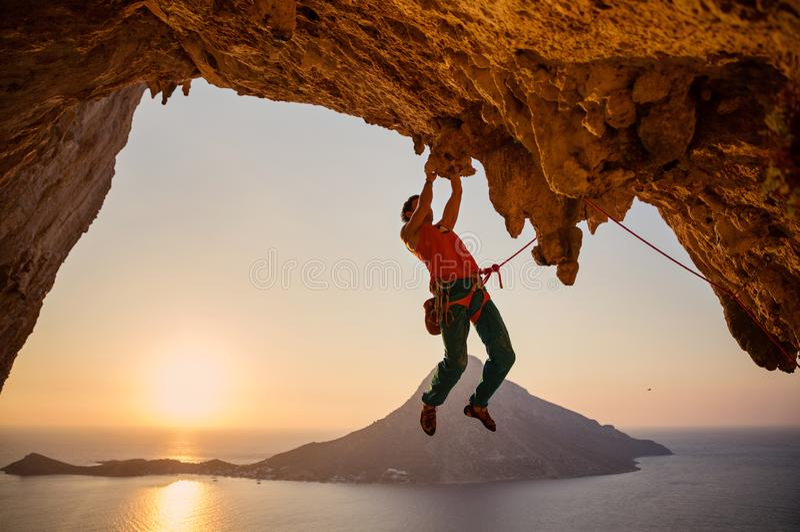 Männlicher Kletterer, der an der Klippe mit einer Hand bei Sonnenuntergang hängt stockfotografie