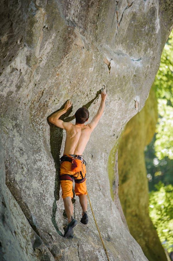 Männlicher Kletterer, der mit Seil auf einer felsigen Wand klettert lizenzfreies stockfoto