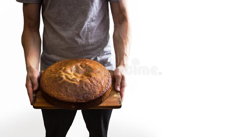 Männlicher Koch, der braunen Apfelkuchen auf einem weißen Hintergrund lokalisiert hält lizenzfreie stockfotos