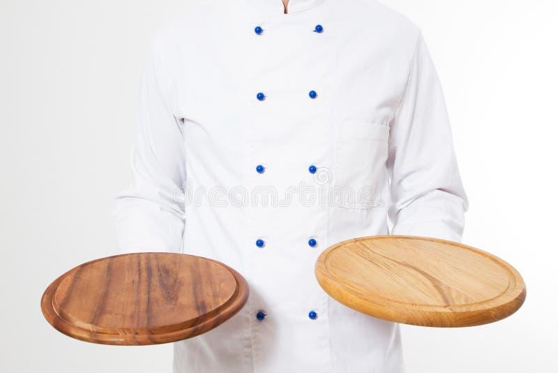 Männlicher Koch, der zwei leere Pizzabretter lokalisiert auf dem weißen Hintergrund, leer hält lizenzfreie stockbilder