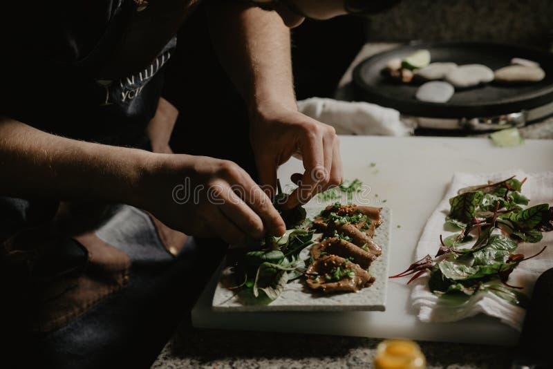 Männlicher Kochchef, der vorbereiteten Salatteller auf der Platte in der Restaurantwerbungsküche schmückend verziert stockfoto