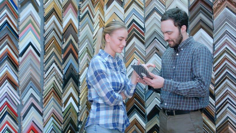 Männlicher Kunde, der dem Verkäufer Bild verwendet die digitale Tablette, nach einem Rahmen suchend im Speicher zeigt lizenzfreies stockfoto