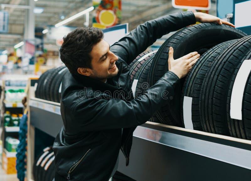Männlicher Kunde, der neue Reifen im Supermarkt wählt stockbilder