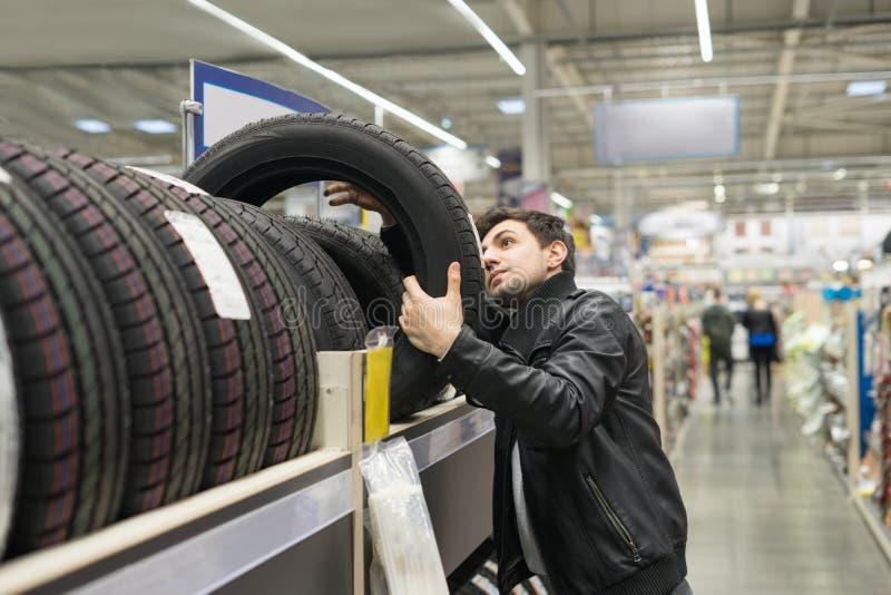 Männlicher Kunde, der neue Reifen wählt lizenzfreies stockfoto
