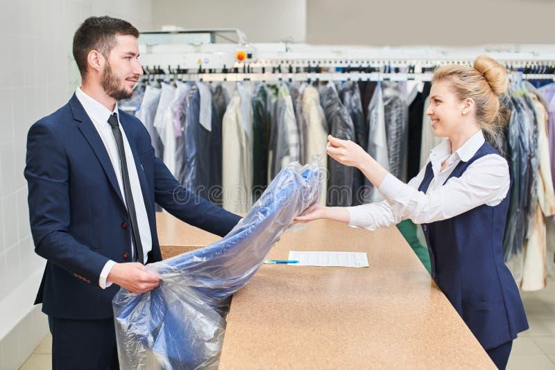 Männlicher Kunde nimmt einer Frau Wäschereiarbeitskraft saubere Kleidung stockfoto