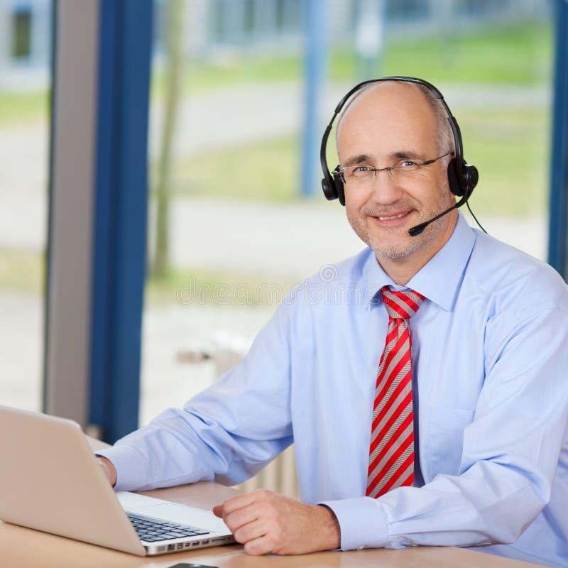 Männlicher Kundendienst-tragender Exekutivkopfhörer bei der Anwendung von Lapt stockbild