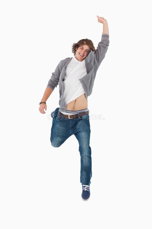 Männlicher Kursteilnehmer, Der Durch Das Springen Mit Einem Angehobenen Arm Aufwirft Lizenzfreies Stockfoto