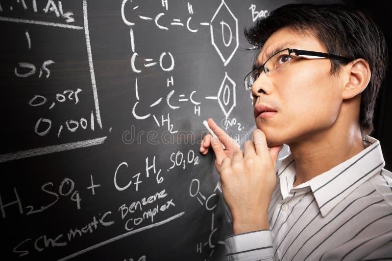Männlicher Kursteilnehmer, der an Gleichung arbeitet stockfotos