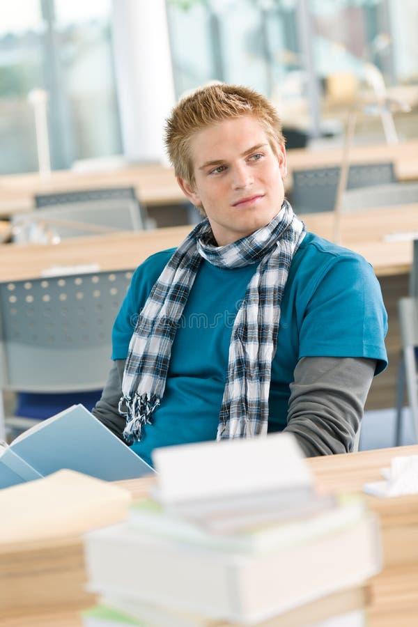 Männlicher Kursteilnehmer mit dem Buch, das im Klassenzimmer sitzt stockbilder