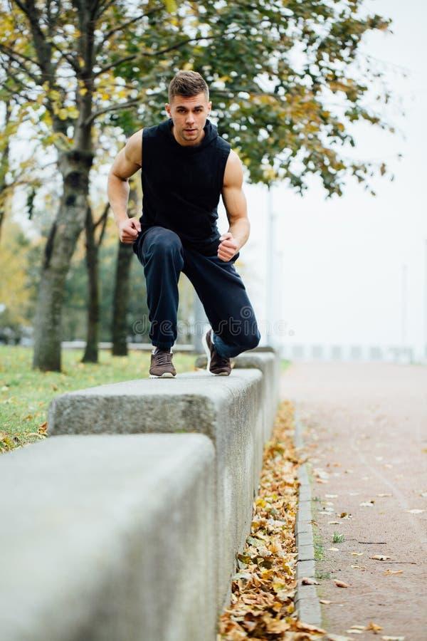 Männlicher Läufer, der Übung, Training im Fallpark tut Drücken Sie ups mit Bank lizenzfreies stockfoto