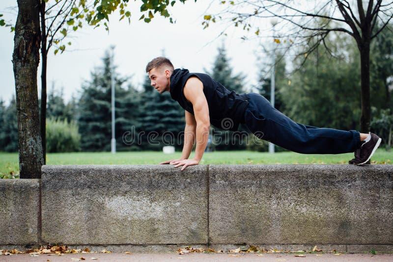Männlicher Läufer, der Übung, Training im Fallpark tut Drücken Sie ups mit Bank lizenzfreies stockbild