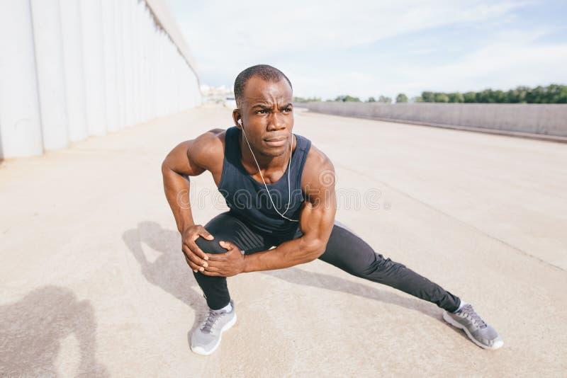 Männlicher Läufer in der schwarzen Sportkleidung, die Beine vor dem Handeln von Morgengymnastik ausdehnt stockbild