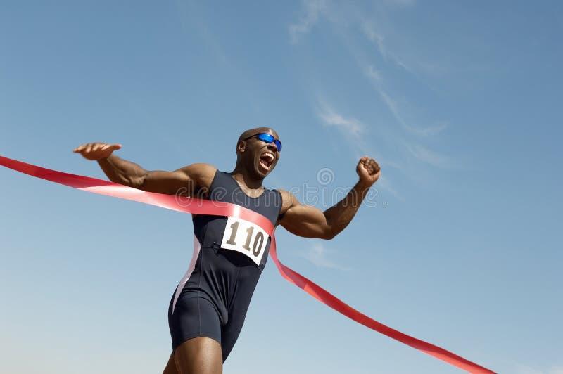 Männlicher Läufer-gewinnendes Rennen stockbilder