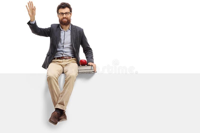 Männlicher Lehrer, der auf einer Platte und einem Wellenartig bewegen sitzt stockbild