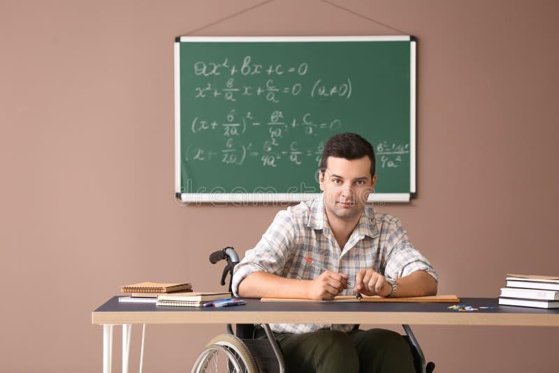 Männlicher Lehrer in der Rollstuhlfunktion bei Tisch im Klassenzimmer lizenzfreie stockbilder