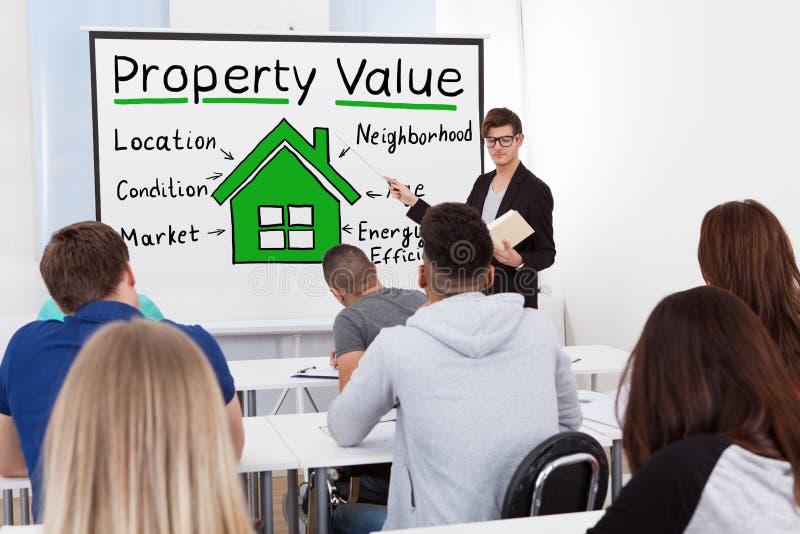 Männlicher Lehrer Teaching Property Value zu den Studenten lizenzfreie stockfotos