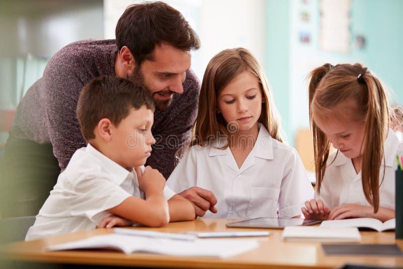 Männlicher Lehrer-With Three Elementary-Schulschüler, die Uniform unter Verwendung Digital-Tablets am Schreibtisch tragen lizenzfreie stockbilder