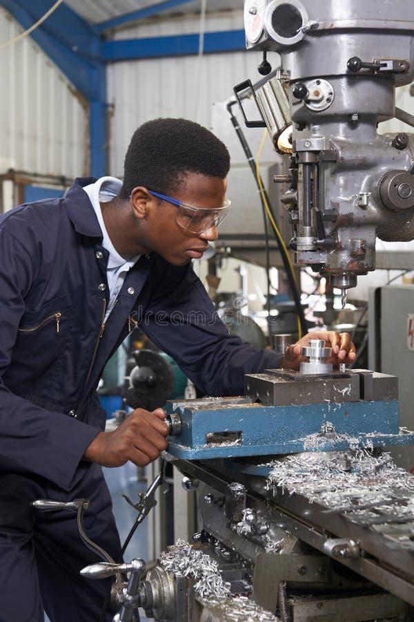 Männlicher Lehrlings-Ingenieur Working On Drill in der Fabrik stockbild