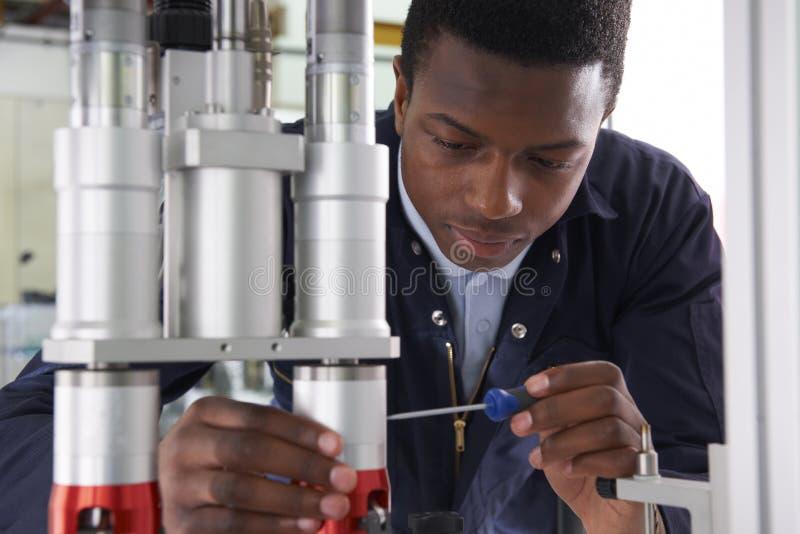 Männlicher Lehrlings-Ingenieur Working On Machine in der Fabrik lizenzfreies stockfoto