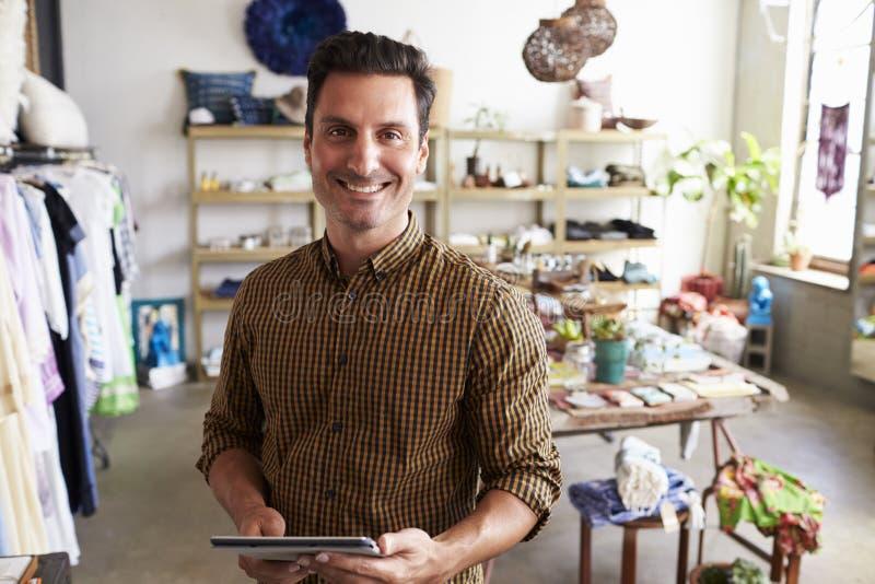 Männlicher Manager mit dem Tablet-Computer, der im Kleidungsshop steht stockbild