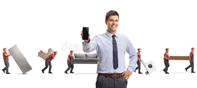 Männlicher Manager mit einem Handy und Urhebern, die Möbel tragen stockbild