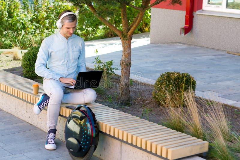 Männlicher MannGeschäftsmann-Studentenfreiberufler mit elektrischem Transport stockfoto