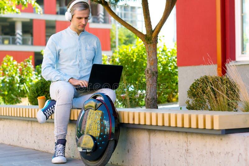 Männlicher MannGeschäftsmann-Studentenfreiberufler mit elektrischem Transport stockbilder