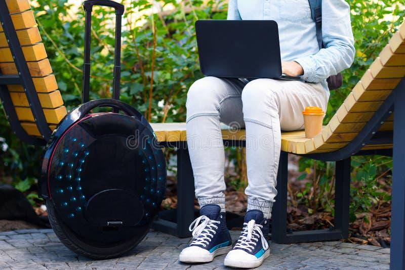 Männlicher MannGeschäftsmann-Studentenfreiberufler mit elektrischem Transport lizenzfreies stockbild