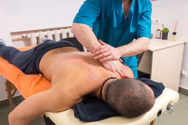 Männlicher Massage-Therapeut zu bemannen Giving Back Massage lizenzfreies stockfoto