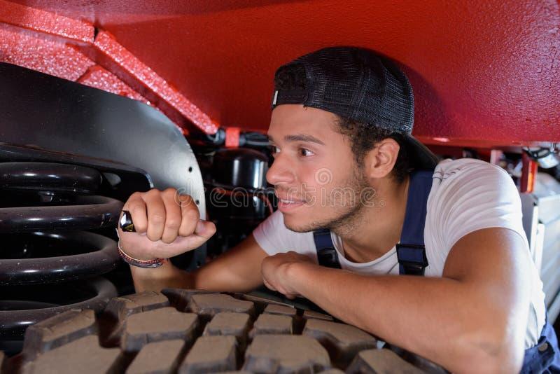 M?nnlicher Mechaniker, der Fackel verwendet, um Fahrzeug zu kontrollieren stockbilder