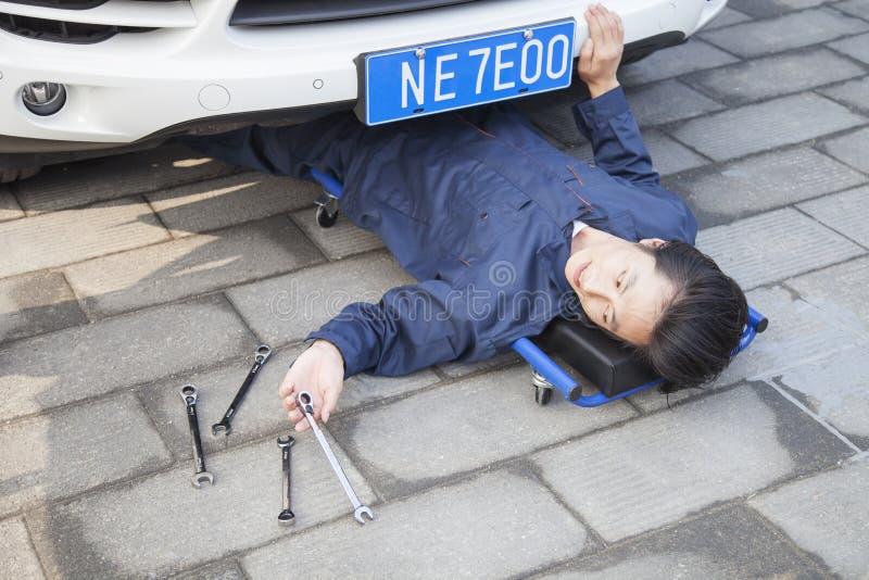 Männlicher Mechaniker, der unter dem Auto arbeitet lizenzfreies stockbild