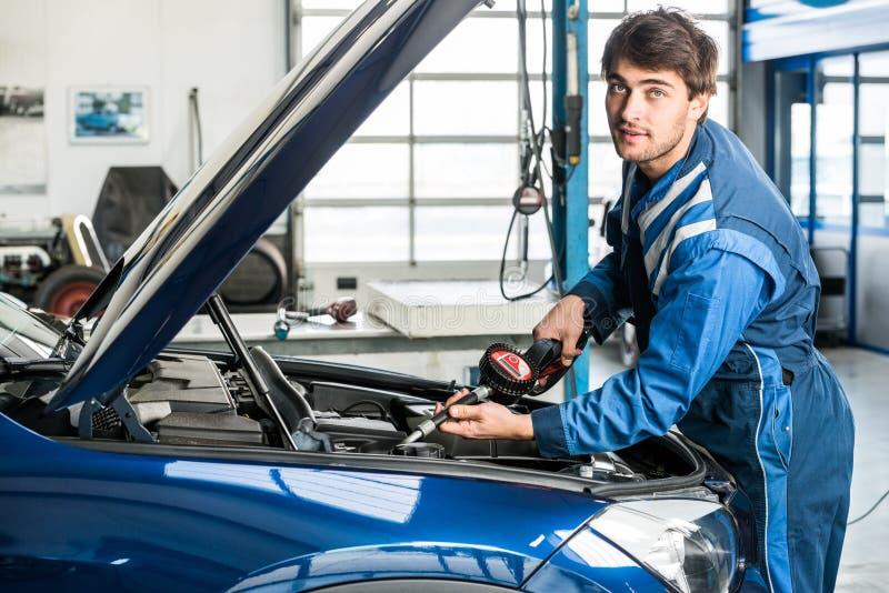 Männlicher Mechaniker Filling Oil Into Car& x27; s-Maschine an der Garage lizenzfreies stockfoto