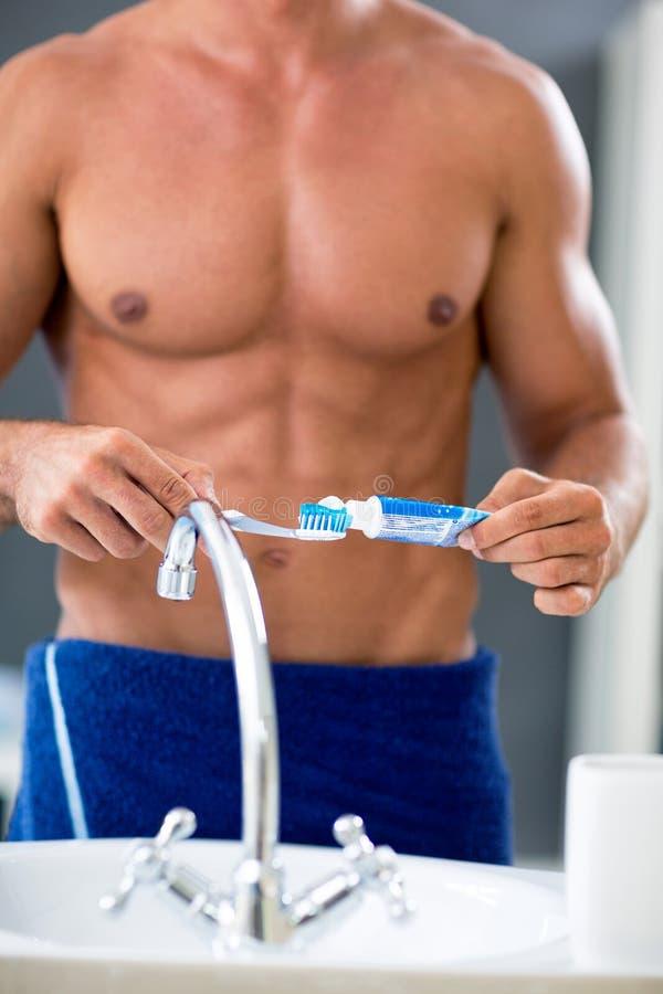 Männlicher nackter Torso von männlichem mit Zahnpasta und Bürste stockbild