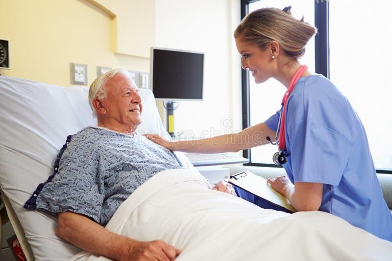 Männlicher Patient Krankenschwester-Talking To Seniors im Krankenhauszimmer stockfotos