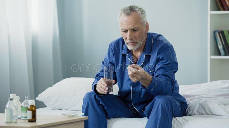 Männlicher Pensionär, der täglichen Vitaminkomplex nimmt, um genito-urinäres System beizubehalten stockfotos