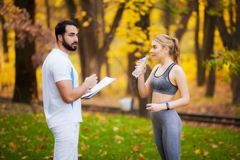 Männlicher persönlicher Trainer, der ihrem weiblichen Kunden Ergebnisse zeigt lizenzfreies stockfoto