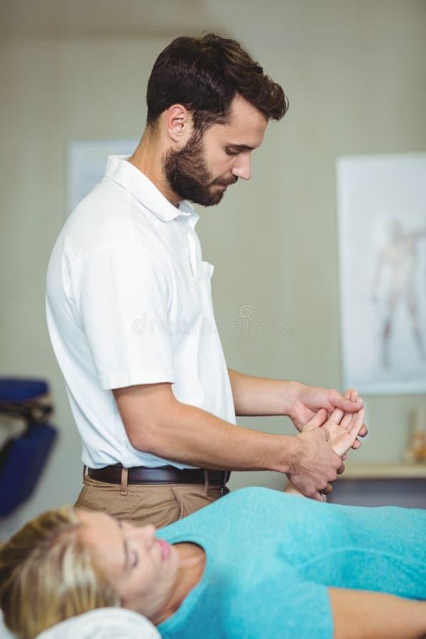 Männlicher Physiotherapeut, der dem weiblichen Patienten Handmassage gibt stockfotografie
