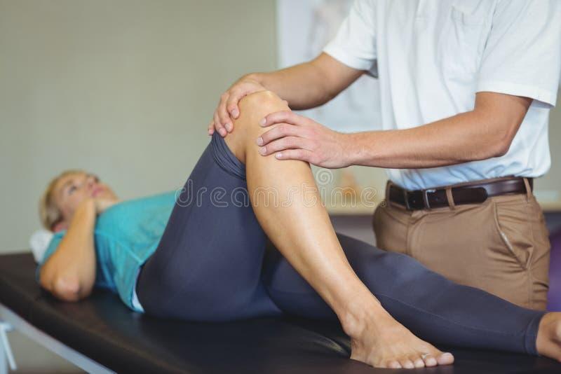 Männlicher Physiotherapeut, der dem weiblichen Patienten Kniemassage gibt lizenzfreies stockfoto