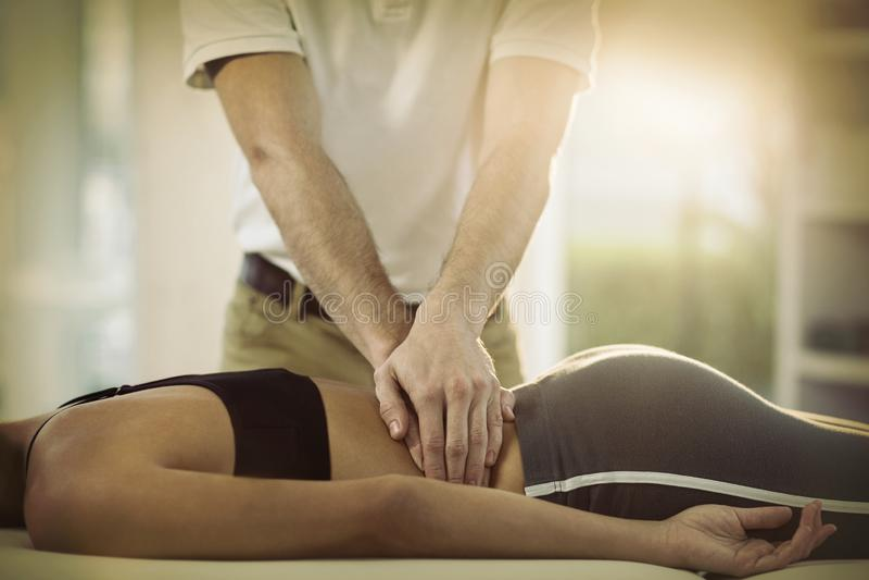 Männlicher Physiotherapeut, der dem weiblichen Patienten Rückenmassage gibt stockfotos