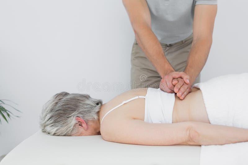 Männlicher Physiotherapeut, der die Rückseite einer älteren Frau massiert stockbilder