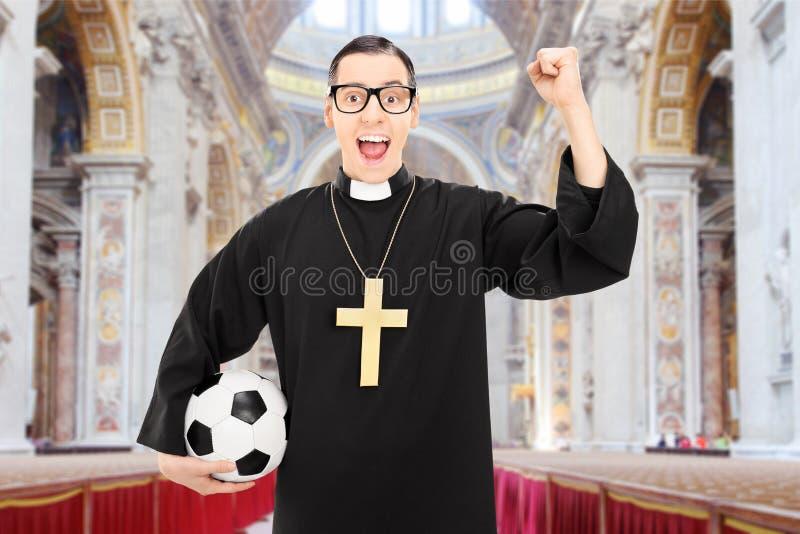 Männlicher Priester mit Fußball zujubelnd in einer Kirche stockfotos