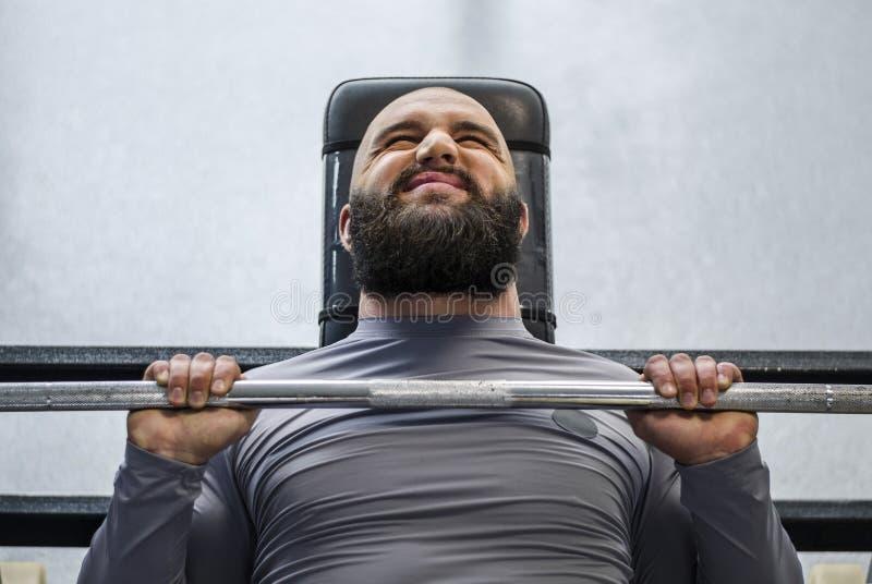 Männlicher Profisportler, der den Barbell, schwer arbeitend vor Wettbewerb bedrängt stockfotos