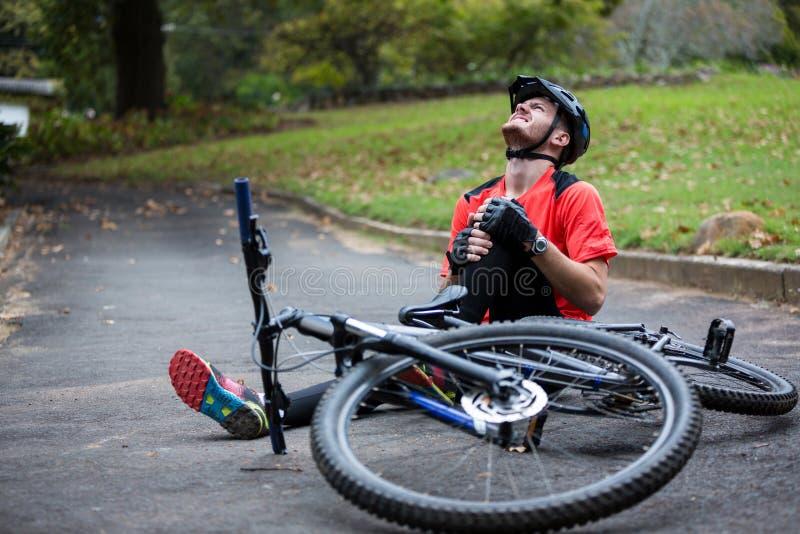 Männlicher Radfahrer, der beim Fallen von der Mountainbike verletzt erhält lizenzfreie stockfotografie