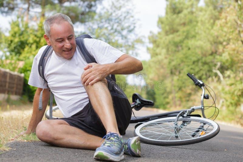 Männlicher Radfahrer, der nach Fahrradunfall verletzt erhält lizenzfreies stockfoto