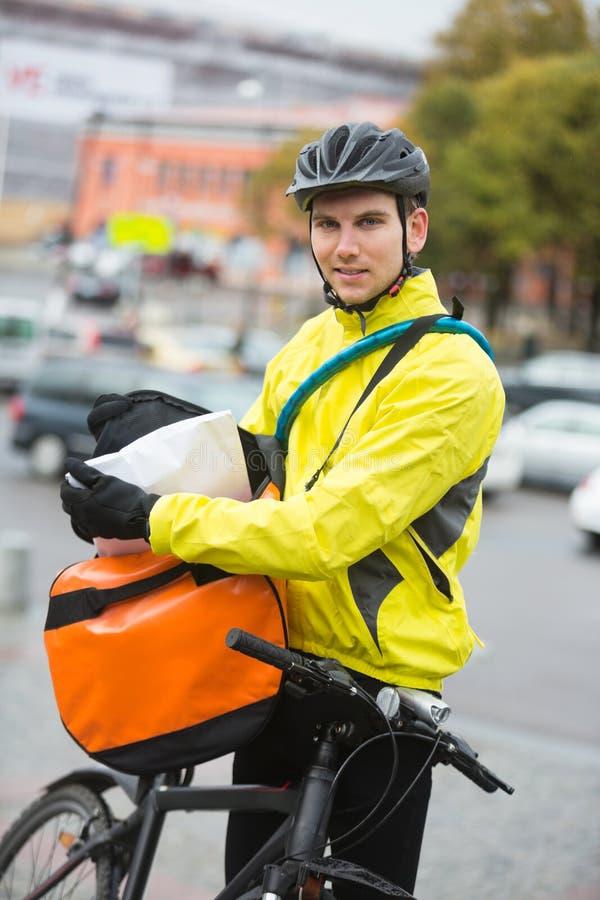 Männlicher Radfahrer, der Paket in Kurier Bag On einsetzt stockfotografie