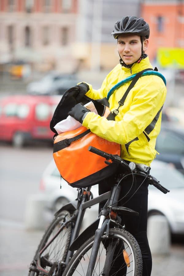 Männlicher Radfahrer, der Paket in Kurier Bag On einsetzt lizenzfreie stockfotos